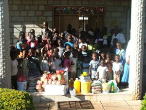 kids receiving food items for christmas from guests